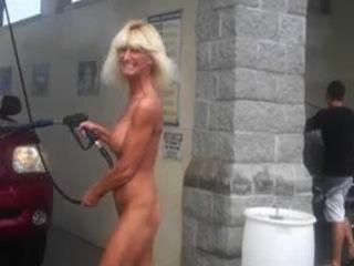 Une blonde platine, aux seins refaits et avec une grosse envie d'exhibitionnisme, se met à poil pour nettoyer sa voiture, en plein jour et en public.