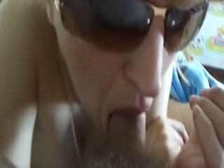 Une coquine, qui reste anonyme en portant des lunettes de soleil, taille une pipe goulue à son mec.