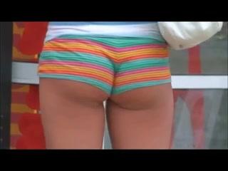 Un voyeur filme de derrière les belles fesses, bien musclées, d'une femme qui se promène en mini short moulant.