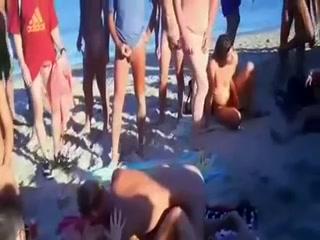 Un couple de chauds libertins s'envoie en l'air sur une plage nudiste devant une horde de voyeur à la bite à l'air.