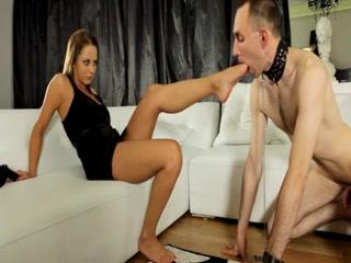 Cette très belle et charmante femme, en robe courte et en talons, dispose d'un esclave qu'elle oblige à lui lécher les pieds.